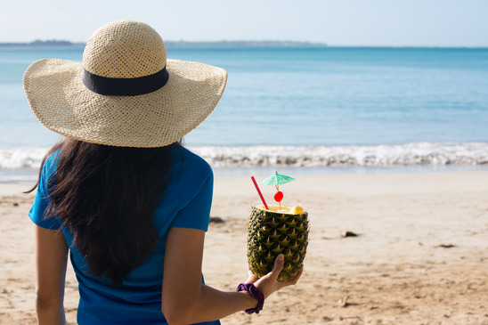 Closeup portrait, woman in blue shirt and brown hat holding pina colada rum pineapple mixed drink with straw and tiny umbrella, while looking out towards beach and ocean